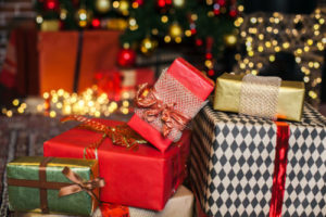 Close up Christmas gift box. Christmas presents in red and brown boxes on Christmas Tree background in loft interior copy space.